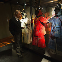 "TREVISO, ITALY - NOVEMBER 12:  Curator Adriano Madaro looks at some of the extremely rare military coats dating from 1644 belonging to the Manchu Army called ""Eight Banners"" at the Case dei Carraresi on November 12, 2011 in Treviso, Italy.  The exhibition called, ""Manchu, The Last Emperor"" will stay open until the 13th May 2012.  (Photo by Marco Secchi/Getty Images)"