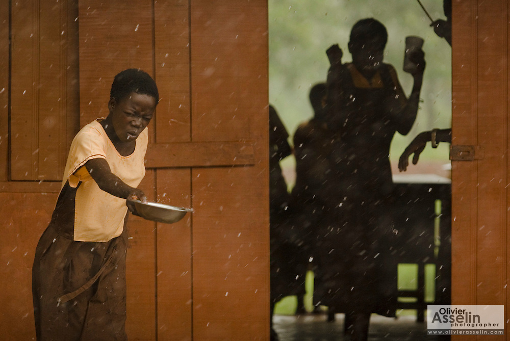 A girl collects rain water in a metal bowl during a downpour at the Nyologu Primary School in the village of Nyologu, northern Ghana, on Wednesday June 6, 2007. ..