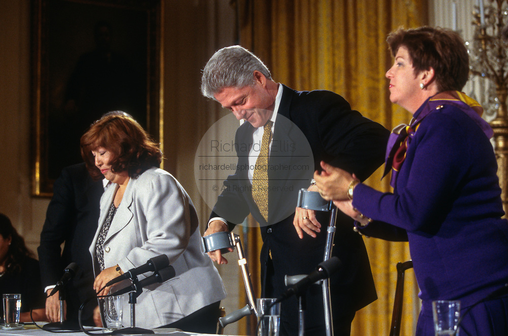 WASHINGTON, DC, USA - 1997/04/02: U.S. President Bill Clinton arrives using crutches for a Roundtable Discussion on Education event in the East Room of the White House April 2, 1997 in Washington, DC.  California Superintendent of Public Education, Delaine Eastin is to the right and California school teacher Carmen Cortez left.   (Photo by Richard Ellis)