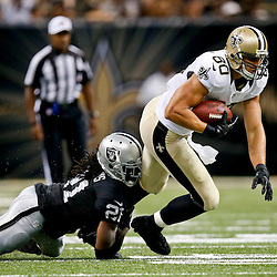 Aug 16, 2013; New Orleans, LA, USA; New Orleans Saints tight end Jimmy Graham (80) is tackled by Oakland Raiders cornerback Mike Jenkins (21) during the second quarter of a preseason game at the Mercedes-Benz Superdome. Mandatory Credit: Derick E. Hingle-USA TODAY Sports