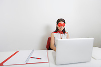 Young businesswoman dressed as superhero using laptop at desk in office