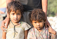 Two little children from a poor family, look sad and destitute and wearing dirty clothes. Nepalganj, Nepal