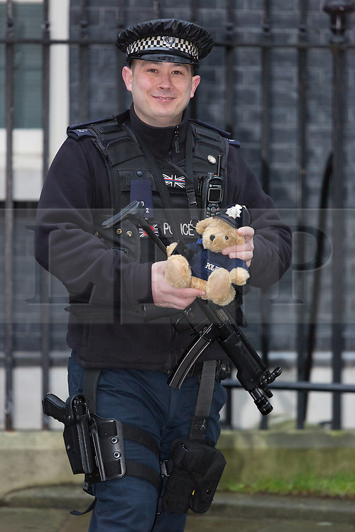 © Licensed to London News Pictures. 15/12/2015. London, UK. Armed police pose for a photograph with Bobby the bear outside 10 Downing Street during a cabinet meeting in Downing Street. Photo credit : Vickie Flores/LNP