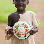 A boy holding the pan he uses to eat lunch walks to school in the village of Ying, Ghana on Wednesday June 6, 2007.