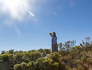 Young woman standing alone on hillside with bright sunshine lens flare blue sky, Spain - model released