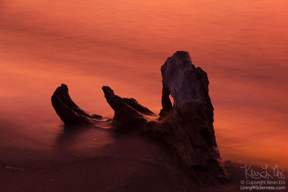 An especially fiery sunset reddens the water of Puget Sound as it crashes up against a large piece of driftwood on the Edmonds, Washington waterfront. A 30-second camera exposure blurs the movement over the water.