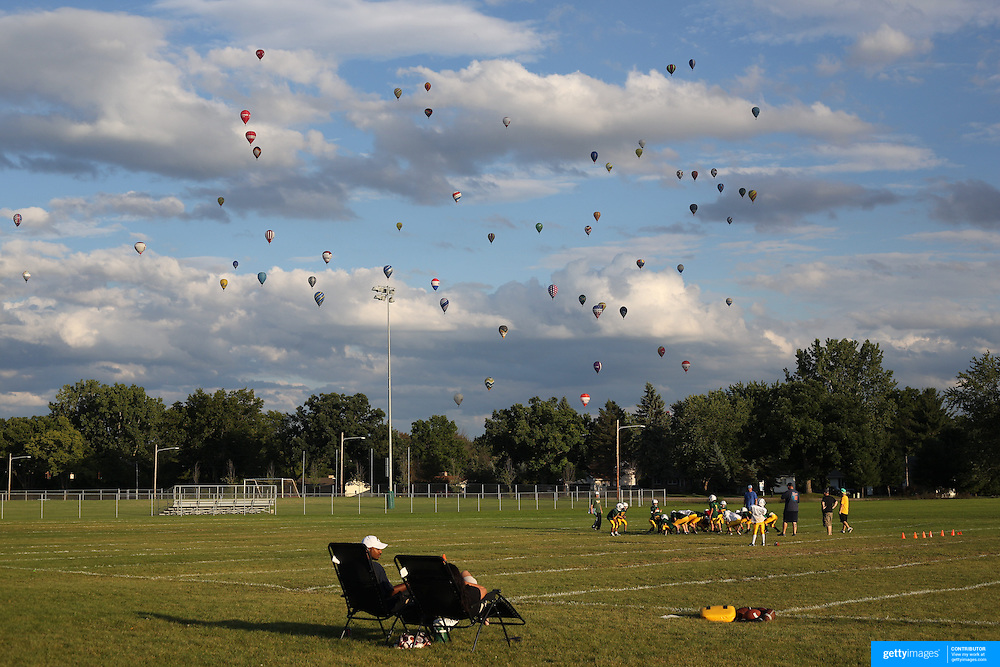 The Pennfield Bombers 5th and 6th grade American Football Team train in the late evening sunshine as Hot Air balloons take to the skies around rural Michigan near Battle Creek during the World Hot Air Ballooning Championships. Battle Creek, Michigan, USA. 20th August 2012. Photo Tim Clayton
