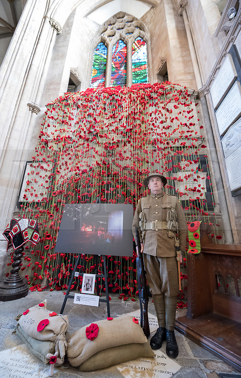 """© Licensed to London News Pictures. 27/10/2018. Bristol, UK. The Royal British Legion launch this year's Poppy Appeal, """"One thousand poppies, for one hundred years, for one million lives"""" at Bristol Cathedral. Picture inside Bristol Cathedral of Somerset Light Infantry re-enactor DAVID HARRIS by a commemoration for Corporal Chris Addis who was killed in Bosnia in 1998. For the launch of the 2018 Bristol Poppy Appeal at 11am on 27 October, The Royal British Legion recreated a scene from the end of WW1 outside Bristol Cathedral on College Green, and Colonel Clive Fletcher-Wood read the war poem In Flanders Fields. They were joined by a Bugler and the Bristol Military Wives Choir who performed songs from their new album 'Remember'. Staff at MOD Filton filled 400 sandbags with eight tonnes of sand to build trenches and recreate 'Flanders Fields' and planted over 1000 waterproof poppies on College Green. Poppies and sandbags can be sponsored by individuals wanting to remember those who fought and died in conflict. There were re-enactors in WW1 uniform from Somerset Light Infantry (known as the West Country Tommys), as well as medics and nurses with equipment from the time. Bristol's own 'War Horse' (Buzz from Blagdon Horsedrawn Carriages) was on College Green behind the improvised barbed wire to represent the 350,000 horses that left Avonmouth for the frontline during WW1. There are also 10,000 knitted poppies on display both in and outside Bristol Cathedral following 'The Charfield Yarn Bombers' incitement to locals to get knitting to mark the occasion, with a display inside the Cathedral organised by Helen Date. Photo credit: Simon Chapman/LNP"""