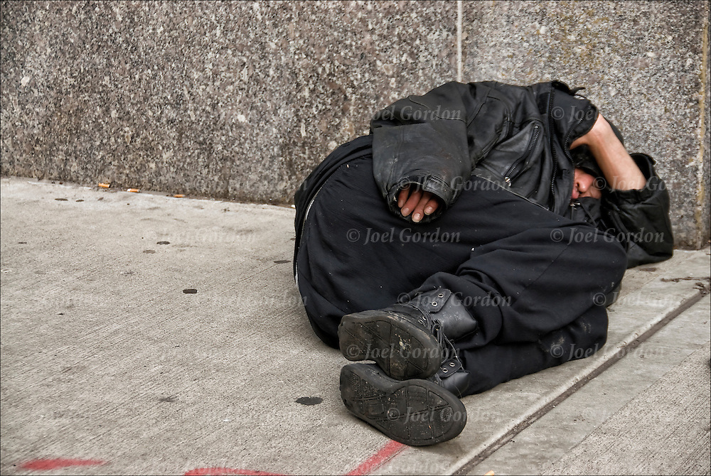 Homeless street person a sleep on the street, begging for handouts in New York City. Homeless person living on the streets appearing depressed  and appearing mentally ill shabbily dressed with evidence of poor hygiene.
