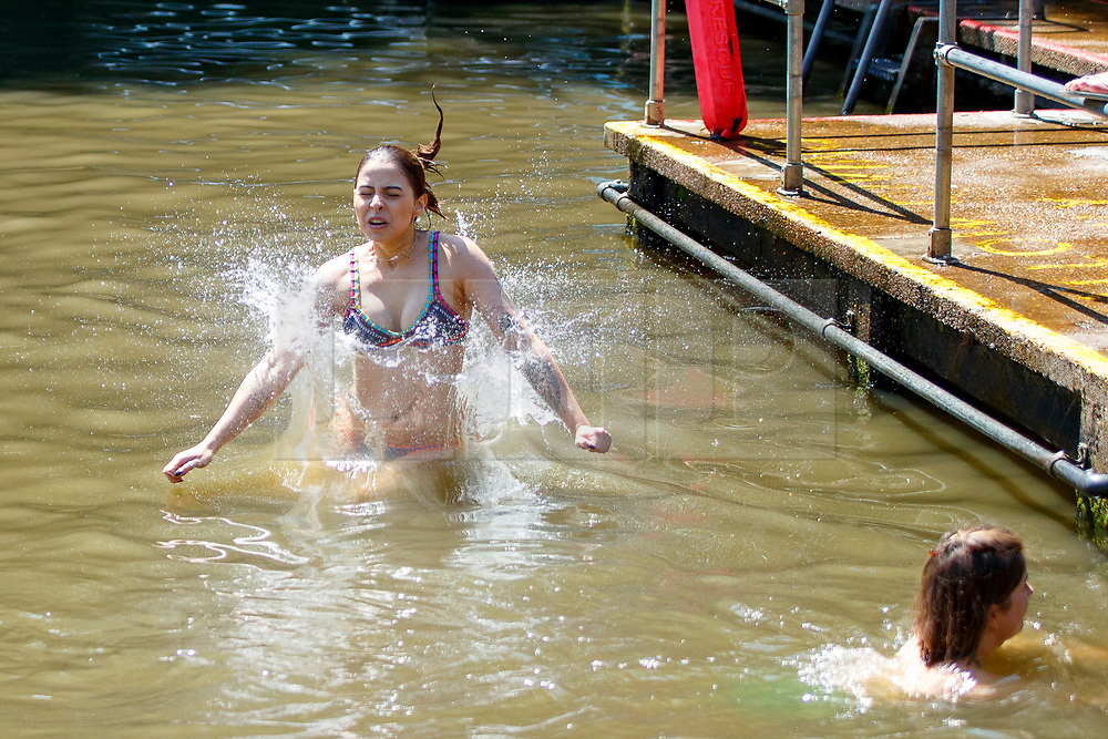 © Licensed to London News Pictures. 05/07/2017. London, UK. Mariana Gaigher jumps into Hampstead Heath Mixed Bathing Pond in north London as temperatures hit 28C degrees on 5 July 2017. Photo credit: Tolga Akmen/LNP