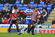 Romaine Sawyers (19) of Brentford and Sergi Canos (7) of Brentford don't like how fast Yakou Meite (21) of Reading is taking to leave the field after being subsituted and try to hurry him up during the EFL Sky Bet Championship match between Reading and Brentford at the Madejski Stadium, Reading, England on 13 April 2019.