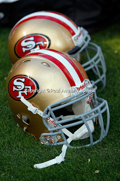San Francisco 49ers helmets lie on the grass during the NFL preseason week 3 football game against the Oakland Raiders on Saturday, August 28, 2010 in Oakland, California. The 49ers won the game 28-24. (©Paul Anthony Spinelli)