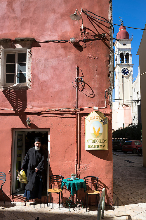 Greek Orthodox priest in traditional robes buying bread from bakery shop in Kerkyra, Corfu Town, Greece