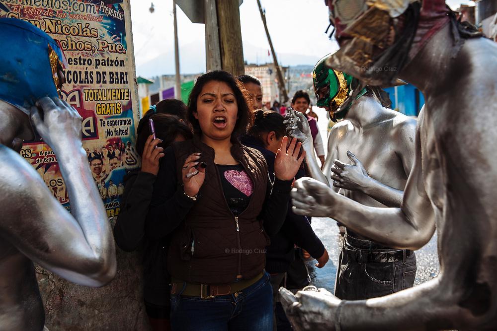 Un grupo de Xinacates con máscaras y el cuerpo pintado intentan manchar la ropa de un grupo de mujeres si no les dan dinero, que ellos ocuparán para su baño al final del día del Carnaval en San Nicolás de los Ranchos.