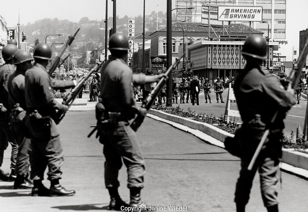 US National guard soldiers with riffles and bayonets take over the town of Berkeley as well as The University of California during The  People's Park student protest & riots in  1969.