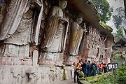 Tourists at Dazu rock carvings of Buddha of Great Sunlight, Buddha of Mercy at Mount Baoding, China