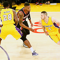 11 October 2016: Los Angeles Lakers guard Marcelo Huertas (4) drives past Portland Trail Blazers guard Damian Lillard (0) on a screen set by Los Angeles Lakers center Tarik Black (28) during the Portland Trail Blazers 109-106 OT victory over the Los Angeles Lakers, at the Staples Center, Los Angeles, California, USA.
