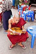 Monk reading at streetside book stall. Yangon, Myanmar.