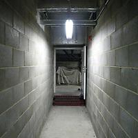 A grey interior corridor leading to a doorway