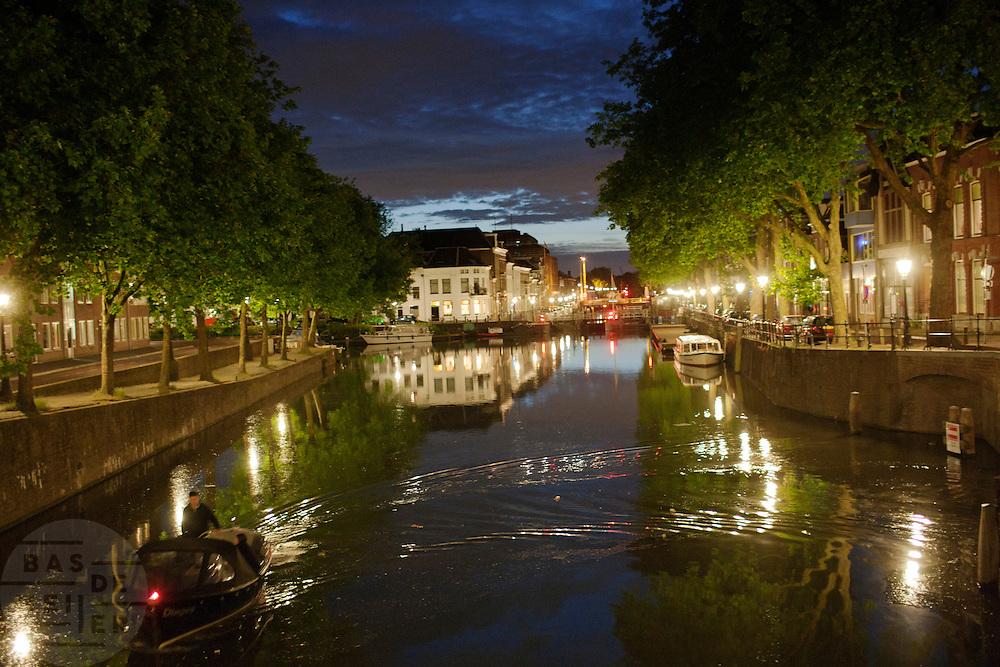 Een man vaart 's avonds laat in een bootje over de Vecht door Utrecht.<br /> <br /> The river Vecht late at night.