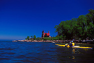 A sea kayaker paddles past the Sand Island Lighthouse in Apostle Islands National Lakeshore near Bayfield, Wis.