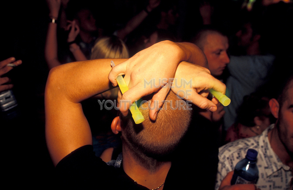 A raver holds two fluorescent glowsticks above his head, U.K, 2000s.