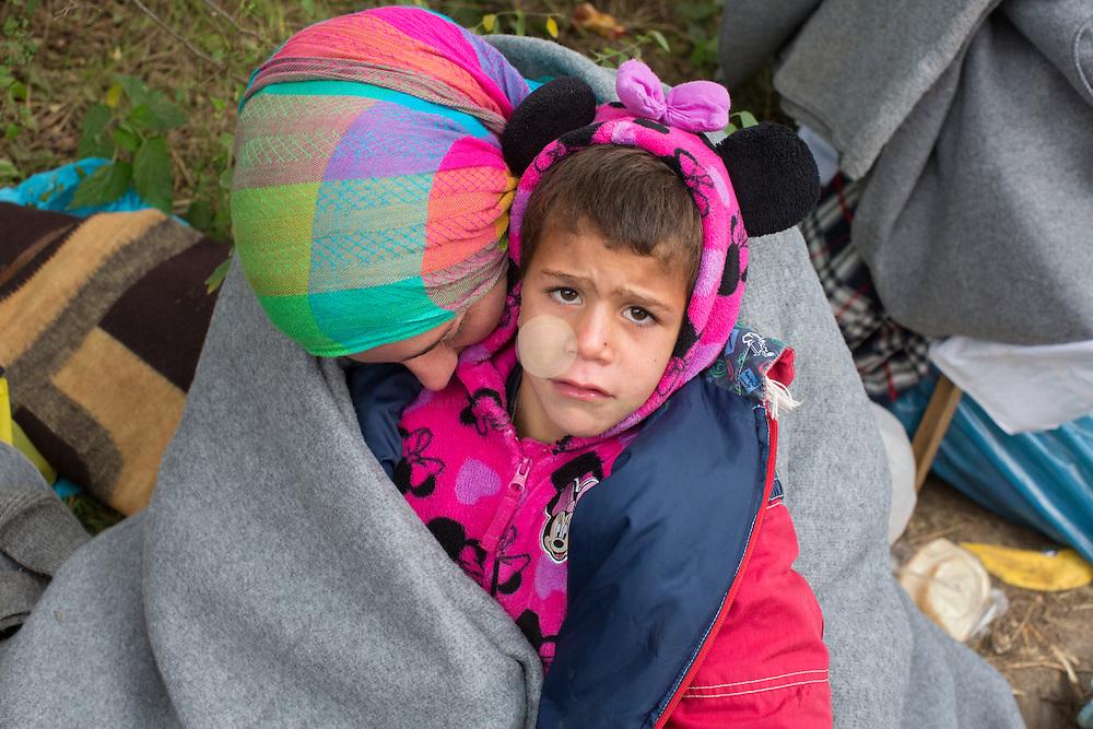 SERBIEN, Grenzstadt Berkasovo, Stadtgebiet von Šid. 08.10.2015 / Fluechtlinge an der serbisch-kroatischen Grenze: Eine Frau wartet mit ihrem Kind auf den Grenzuebertritt, im eisigen Herbstwind. Die kroatische Grenze, und damit die EU-Aussengrenze, ist nur noch 100 Meter entfernt. Der Grenzuebertritt erfolgt zu Fuss und in Gruppen zu etwa 50 Personen.