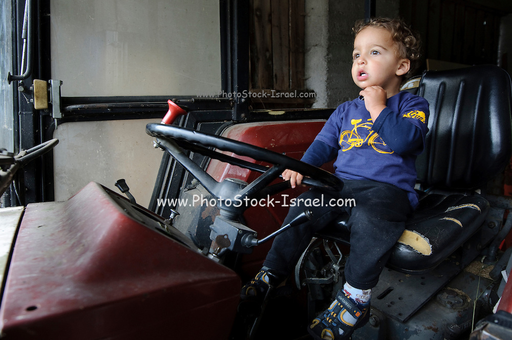 A young boy of 2 sits on a tractor