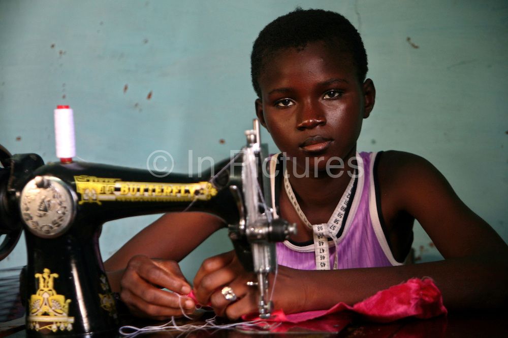 A young 14-year-old Malian girl from the street project of the Jeunesse & Developpement project learns how to sew in Bamako; Mali. The J&D project supports the empowerment of local communities, the improvement of education, and the promotion of health and economic development.