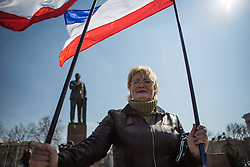 Crimea one day before the referendum. A lady holds a Crimean flag with a statue of Lenin in the background in a pro Russian rally at Simferopol's Lenin Square. Simferopol, . Saturday, 15th March 2014. Picture by Daniel Leal-Olivas / i-Images