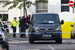 Coroners cover a body from a forensics tent in Cathcart Road, Chelsea, following the fatal stabbing on the night of May 30th 2018 of a man in his forties, said to be a delivery driver who refused to hand over his cash to robbers. London, May 31 2018.