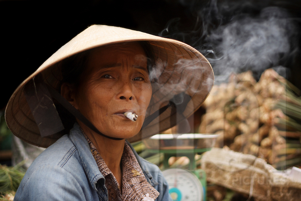 A vietnamese woman smokes a cigarette on a local market of Hue, Vietnam, Southeast Asia