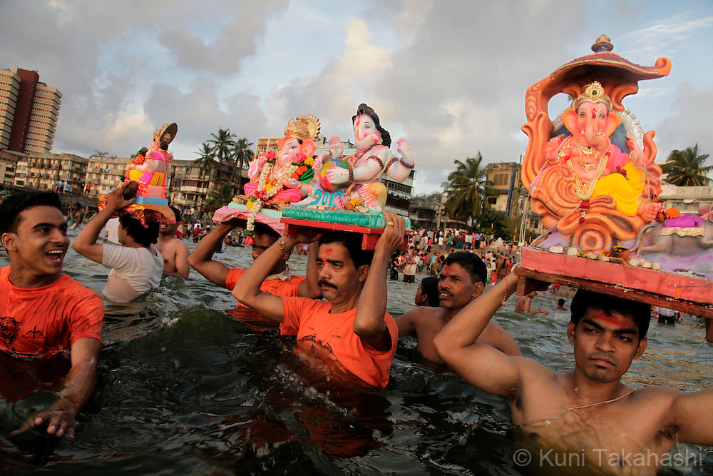 Hindu devotees immerse ganesha idols into the sea in Mumbai, India on Sep 15, 2010 on the 5th day of Ganpati festival. The 10-day hindu festival, celebrating the birthday of Lord Ganesha who is widely worshiped as the god of wisdom, prosperity and good fortune, attracts tens of thousands people..Photo by Kuni Takahashi