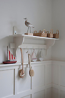 Bird statue and baskets on bathroom shelf London