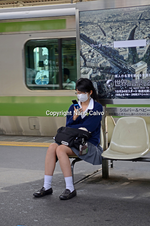 Schoolgirl wearing mask and using mobile phone in train station, Tokyo, Japan
