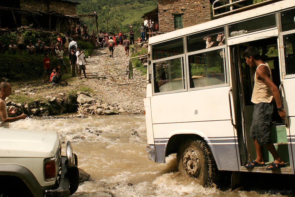 A conductor whistles to the driver of this local bus as they navigate a flooded river in the Sindhupalchok District. www.crystalstreet.net