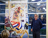 Garden City, New York, USA. March 9, 2019. Artist MICHAEL WHITE, standing next to his mural of the lead horse of historic Nunley's Carousel, gives info about the acrylic mural during its Unveiling Ceremony held at Nunley's Carousel Pavilion, Long Island. The mural, an approx. seven feet tall by five feet wide, 7'x5', will be installed on a trestle pillar outside Baldwin Train Station.