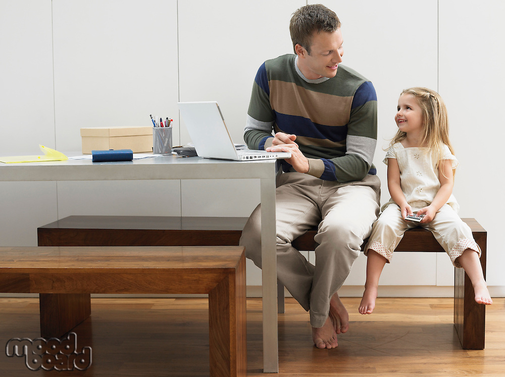 Father and daughter using laptop and cell phone