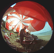 Man DJing outside under red and white canopy, Free Party, Bolongna, 2000's,