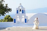 Bride walking past church,Santorini, Kyclades,South Aegean, Greece,Europe