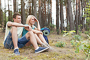 Full length of young hiking couple relaxing in woods