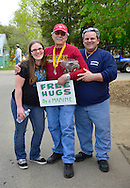 April 28, 2013 - Floral Park, New York, U.S. -  At center, Marine JOHN GIORDANA, of Whitestone, a Korean War Vet, gives a Free Hug to smiling visitors at the Marine Corps League's booth collecting donations for veterans, at the Antique Auto Show on the farmhouse grounds of Queens County Farm Museum.