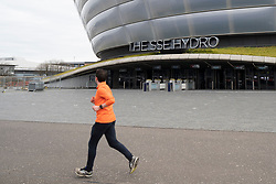 Glasgow, Scotland, UK. 3 April, 2020. Jogger runs  past SSE hydro during building of temporary  NHS Louisa Jordan field hospital at the Scottish Events Campus (SEC) in Glasgow.  Iain Masterton/Alamy Live News