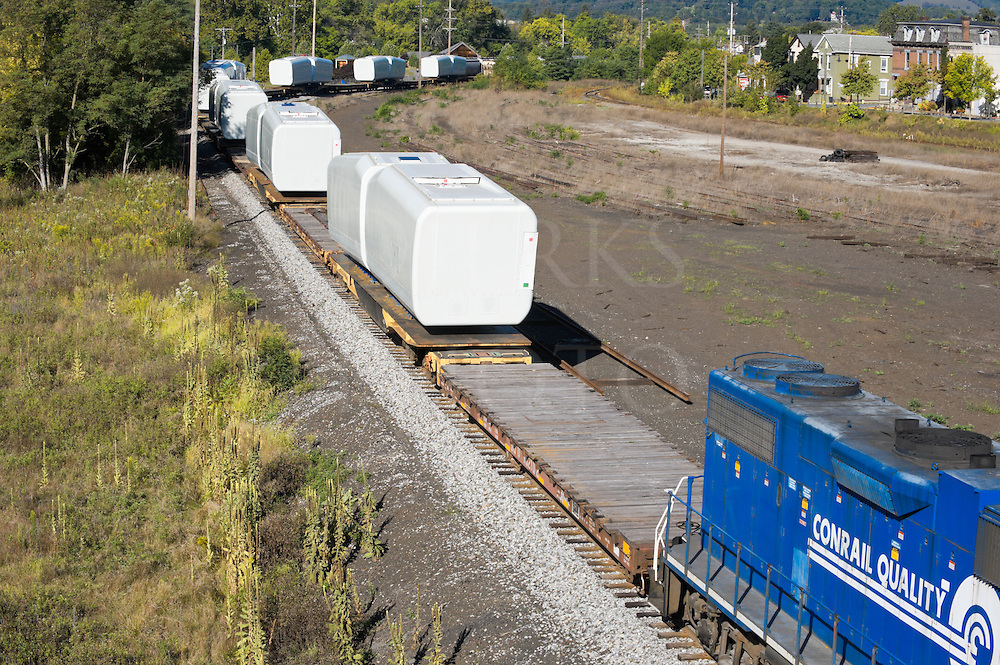 Wind turbine nacelles loaded on flatcars being moved by railroad train away from assembly plant, manufacturing and distribution of large parts for alternative energy.