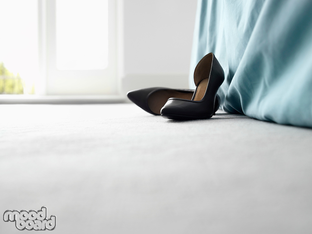 High heeled shoes by bed surface view