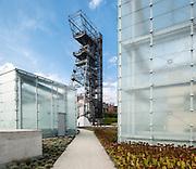 Glass cubes in landscaped garden with mining tower beyond. Silesian Museum, Katowice, Poland. Architect: Riegler Riewe Architekten , 2014.
