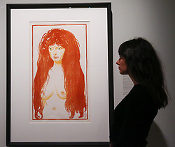 "© Licensed to London News Pictures. 08/04/2019. London, UK. A staff member views Edvard Munch's ""Woman with Red Hair and Green Eyes: Sin, 1902"". Munch had used an unknown model for this print. Her direct pose and piercing expression are intentionally striking, giving her a psychological intensity, but her features are deliberately generalised. With her red hair and green eyes, she bears a resemblance to Tulla Larsen, to whom<br /> he was briefly engaged. By emphasising her abundant red hair, he has conveyed something of the stifling attraction he felt during his tumultuous relationship with Larsen. <br /> <br /> The work of Norwegian artist Edvard Munch (1863-1944) - ""Edvard Munch: love and angst"" at the British Museum opens from 11 April until 21 July 2019. The exhibition focus on Munch's remarkable and experimental prints – an art form which made his name and at which he excelled throughout his life – and will examine his unparalleled ability to depict raw human emotion. It will be the largest exhibition of Munch's prints in the UK for 45 years. Photo credit: Dinendra Haria/LNP"