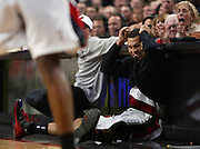 The Blazers' Brandon Roy (7) squirms on the court while waiting to enter the game as the battle rages on under the basket. The Blazers beat the Rockets 107-103.. .