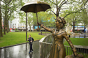 UNITED KINGDOM, London: 28 April 2020 <br /> A member of the public jogs past a statue of Mary Poppins in Leicester Square during a wet and miserable afternoon. The weather is set to stay wet for the next few days according to the Met Office.