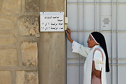 © Licensed to London News Pictures. Hamdaniyah, Iraq. 25/07/2014. Hamdaniyah, Iraq. A Christian nun rings the doorbell of a doctor's surgery in the Iraqi Christian town of Hamdaniyah. Although located close to the front line with the Islamic State the relatively peaceful town has seen over 600 Christian families arrive from nearby Mosul, with many crammed into unfinished houses.<br /> <br /> Having taken over Mosul Iraq's second largest city in June 2014, fighter of the Islamic State (formerly known as ISIS) have systematically expelled the cities Christian population. Despite having been present in the city for more than 1600 years, Christians in the city were given just days to either convert to Islam, pay a tax for being Christian or leave; many of those that left were also robbed at gunpoint as they passed through Islamic State checkpoints.. Photo credit : Matt Cetti-Roberts/LNP